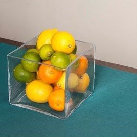 Glass vase with oranges, limes and lemons
